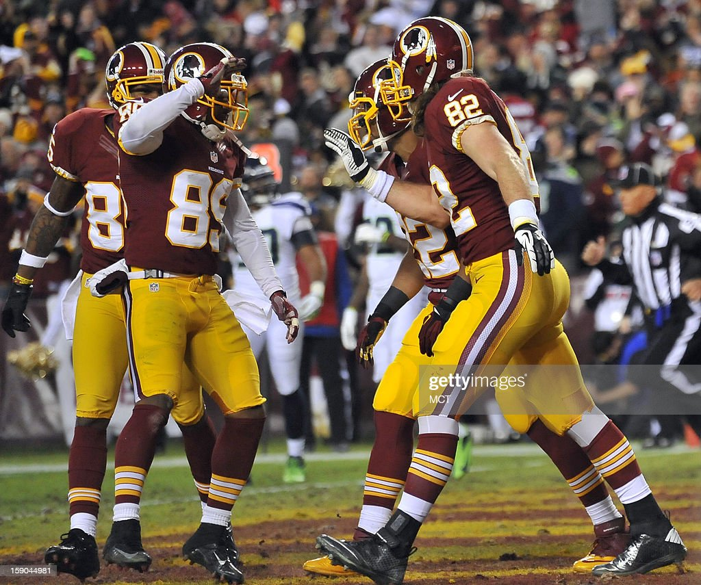 Washington Redskins tight end Logan Paulsen (82) celebrates with Redskins wide receiver Santana Moss (89) and other teammates, after he scored a touchdown against the Seattle Seahawks in the first quarter of an NFC wild-card playoff game at FedEx Field in Landover, Maryland, Sunday, January 6, 2012.