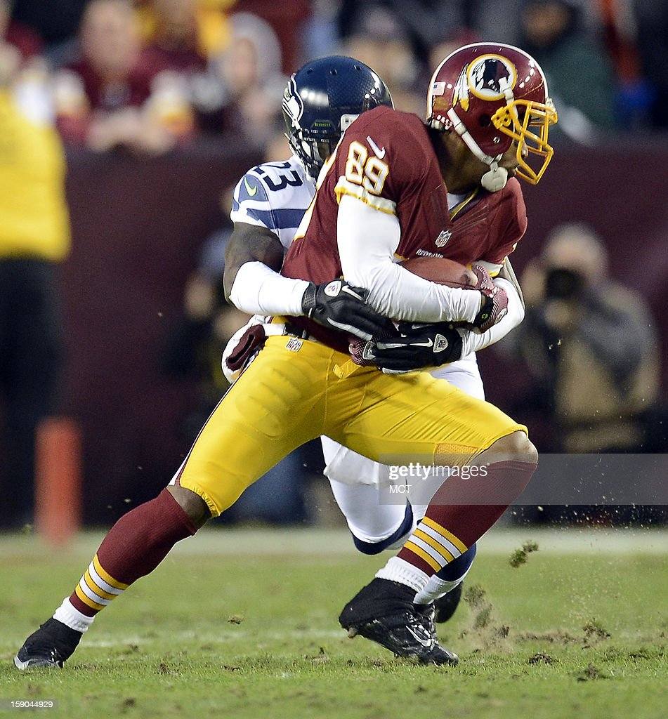 Washington Redskins wide receiver Santana Moss (89) gets tackled by Seattle Seahawks cornerback Marcus Trufant (23) after a catch in the first quarter of an NFC wild-card playoff game at FedEx Field in Landover, Maryland, Sunday, January 6, 2013.