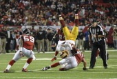 Washington Redskins wide receiver Santana Moss is upended by Atlanta Falcons strong safety Zeke Motta after a first down with under 40 seconds left...