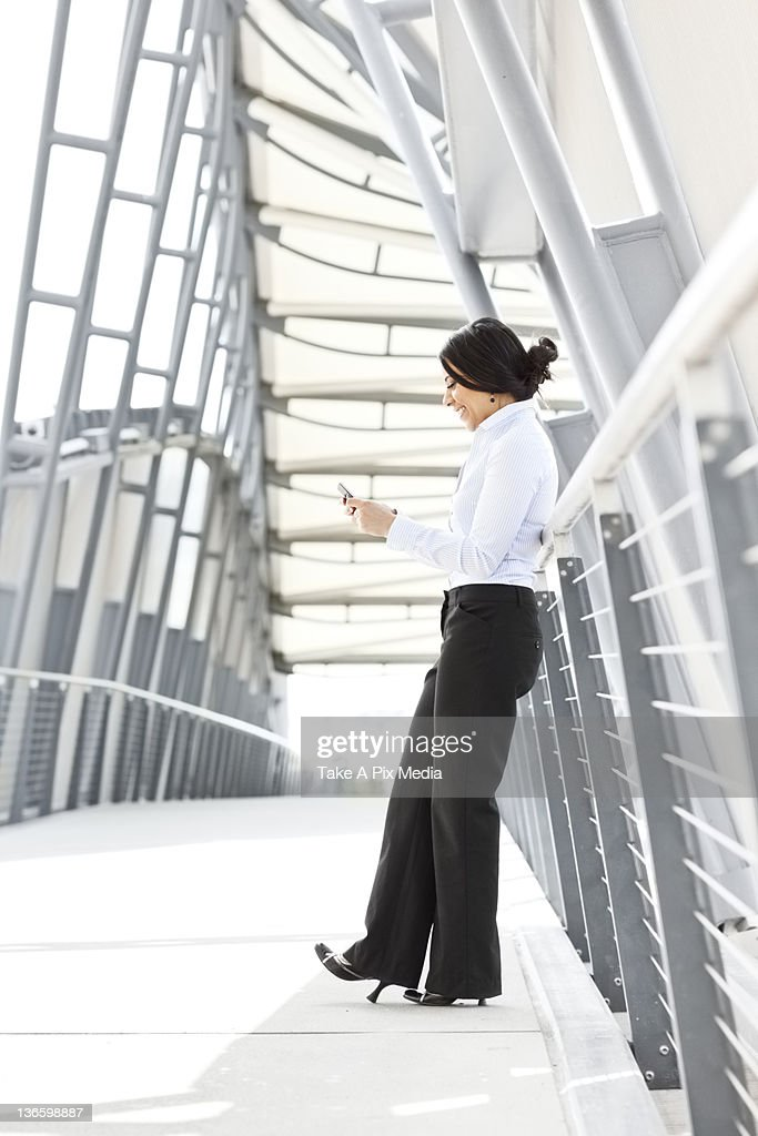 USA, Washington, Seattle, Young businesswoman on walkway, using cell phone : Stock Photo