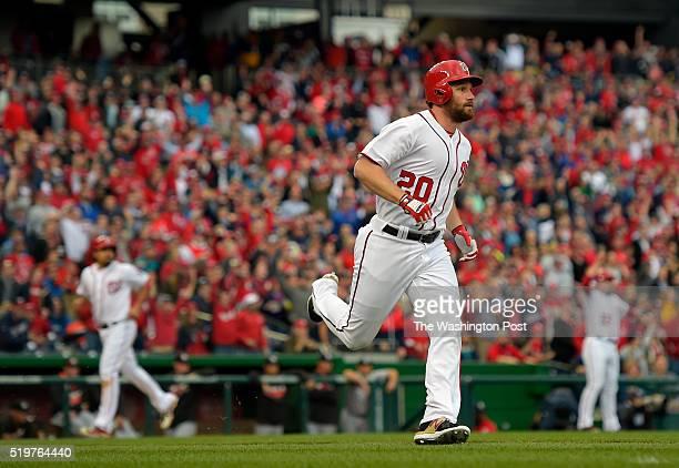 Washington second baseman Daniel Murphy center watches his 1st inning 3 run RBI triple as Washington second baseman Anthony Rendon left heads for...