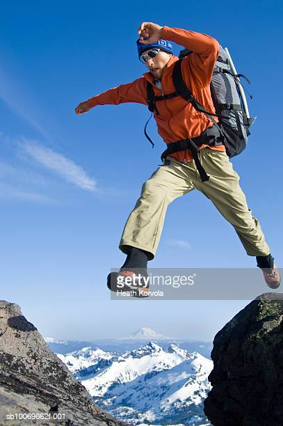 USA, Washington State, Cascade Mountains, Hiker jumping over gap in mountains, low angle view