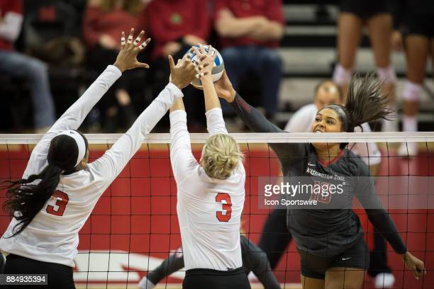 Washington State outside hitter Taylor Mims tries to hit the ball pass Nebraska setter Kelly Hunter and Nebraska middle blocker Briana Holman in the...