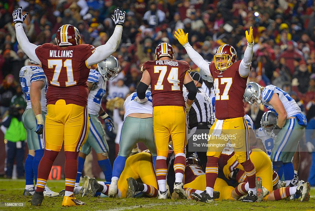 Washington tackle Trent Williams (71), left, and Washington tight end Chris Cooley (47), right, signal touchdown on a late 4th quarter score by Washington running back Alfred Morris forthe game clincher as the Washington Redskins defeat the Dallas Cowboys 28 - 18 for first place of the NFC East division and a playoff spot at FedEx in Landover MD, December 30, 2012 .