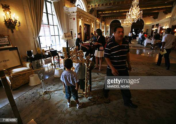 A boy looks in a mirror as prospective buyers peruse sample furniture available during a liquidation sale in the lobby of the Saint Regis Hotel 08...