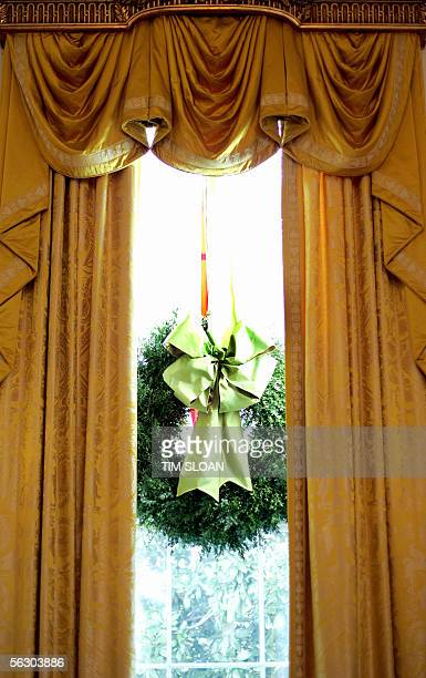 Boxwood wreaths entwined with lime and gold ribbons adorn the first floor windows of the main house and East Wing 30 November 2005 at the White House...