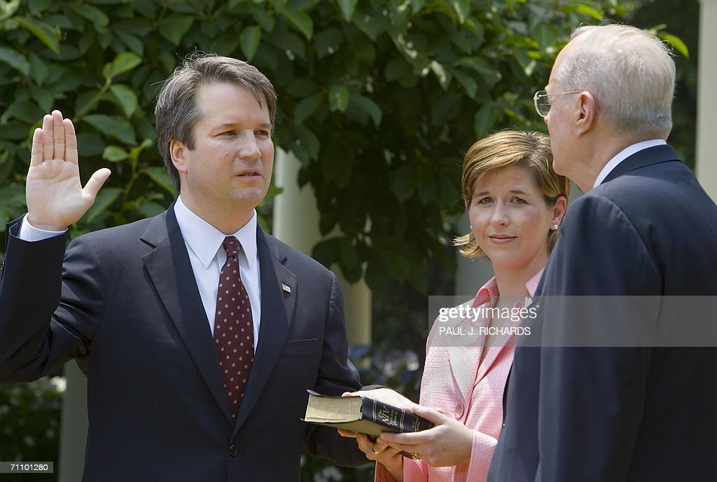 Brett Kavanaugh (L) is sworn in as a US Court of Appeals Judge for the District of Columbia by US Supreme Court Justice Anthony Kennedy (R) as Kavanaugh's wife Ashley (C) holds the Bible during ceremonies 01 June 2006 in the Rose Garden of the White House in Washington, DC. AFP Photo/Paul J. Richards