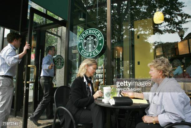 Patrons talk outside a Starbucks store 22 September 2006 in Washington DC The Seattlebased chain announced that it would be raising the price of its...
