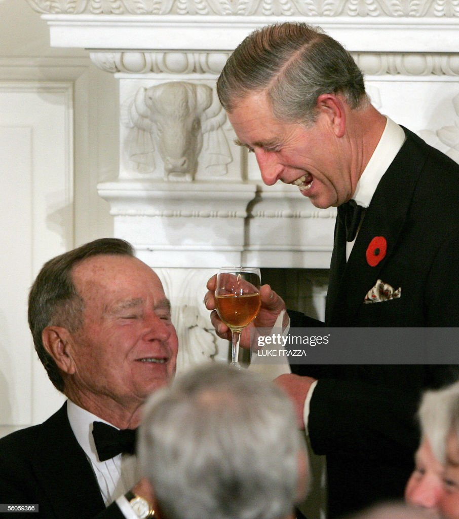 The Prince of Wales (R) jokes with former US president George H. W. Bush after the Prince offered a toast to US President George W. Bush and First Lady Laura during a social dinner at the White House 02 November 2005 in Washington, DC. The Prince and his wife Camilla, Duchess of Cornwall, are on a US tour of goodwill diplomacy and promotion of their pet social projects. AFP PHOTO/Luke FRAZZA