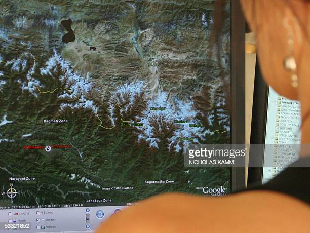 TO GO WITH AFP STORY 'AFPLIFESTYLEUSINTERNETGOOGLE' A woman looks at a view of the snowcovered Himalaya mountains on Google Earth in Washington 03...