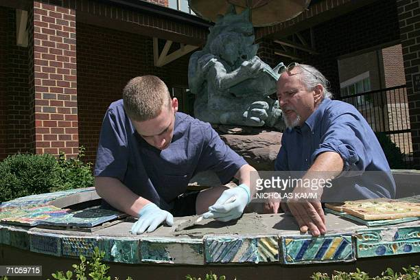 TO GO WITH AFP STORY USSOCIETYEDUCATIONHEALTHCHILDREN The Lab School teacher Mark Jarvis helps a student spread grout as they lay tiles on a fountain...