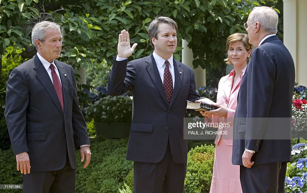 US President George W. Bush (L) watchs as Brett Kavanaugh (C) is sworn in as a US Court of Appeals Judge for the District of Columbia by US Supreme Court Justice Anthony Kennedy (R) as Kavanaugh's wife Ashley holds the Bible during ceremonies 01 June 2006 in the Rose Garden of the White House in Washington, DC. AFP Photo/Paul J. Richards