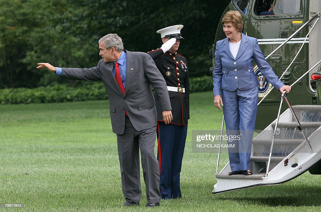US President George W. Bush waves to wellwishers while his wife Laura looks on as they step off Marine One on the South Lawn of the White House in Washington,DC 24 July 2007 upon returning from Charleston Air Force Base in South Carolina.AFP PHOTO/Nicholas KAMM