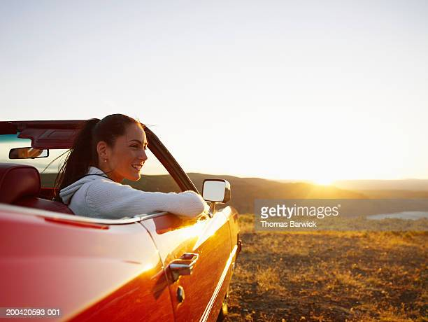 USA, Washington, Vantage, woman in car beside river gorge, sunset