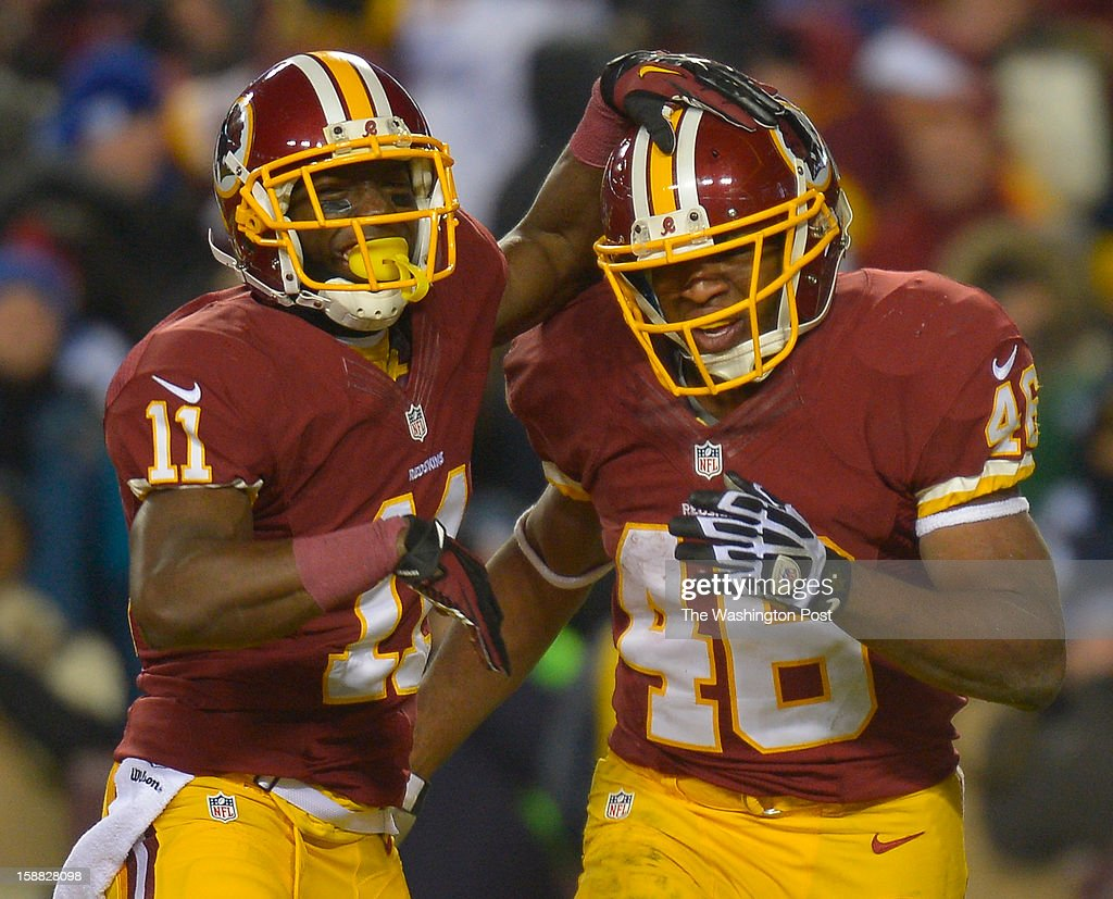 Washington wide receiver Aldrick Robinson (11) congratulates Washington running back Alfred Morris (46) after Morris scored a third-quarter touchdown as the Washington Redskins play the Dallas Cowboys for first place of the NFC East division and a playoff spot at FedEx in Landover MD, December 30, 2012 .