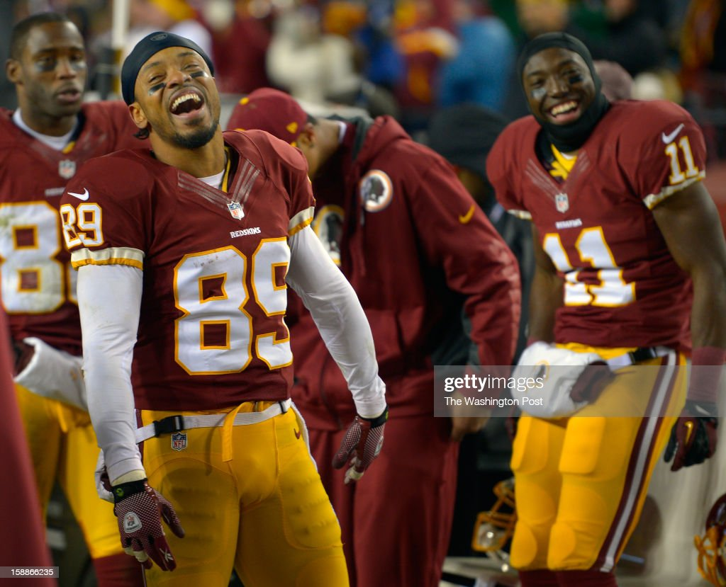 Washington wide receiver Santana Moss (89), 2nd left, laughs wiht wide receiver Aldrick Robinson (11), right, in the last minute of thegame as the Washington Redskins defeat the Dallas Cowboys 28 - 18 for first place of the NFC East division and a playoff spot at FedEx in Landover MD, December 30, 2012 .