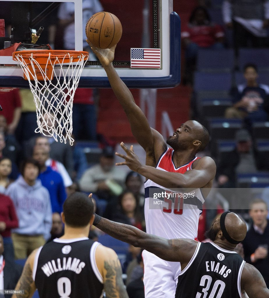 Washington Wizards center Emeka Okafor scores over Brooklyn Nets point guard Deron Williams and power forward Reggie Evans during the first half of...