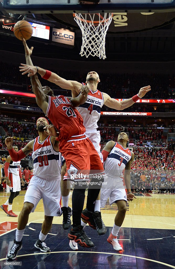 Washington Wizards center Marcin Gortat (4) fouls Chicago Bulls guard <a gi-track='captionPersonalityLinkClicked' href=/galleries/search?phrase=Jimmy+Butler+-+Basketball+Player&family=editorial&specificpeople=9860567 ng-click='$event.stopPropagation()'>Jimmy Butler</a> (21) during second half action as the Washington Wizards play the Chicago Bulls in game three of the Eastern Conference quarterfinals at the Verizon Center on April 25, 2014 in Washington, DC.