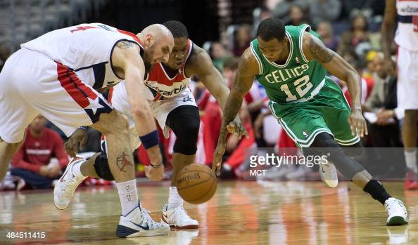 Washington Wizards center Marcin Gortat left Kevin Seraphin and Boston Celtics small forward Chris Johnson go after a loose ball during the first...