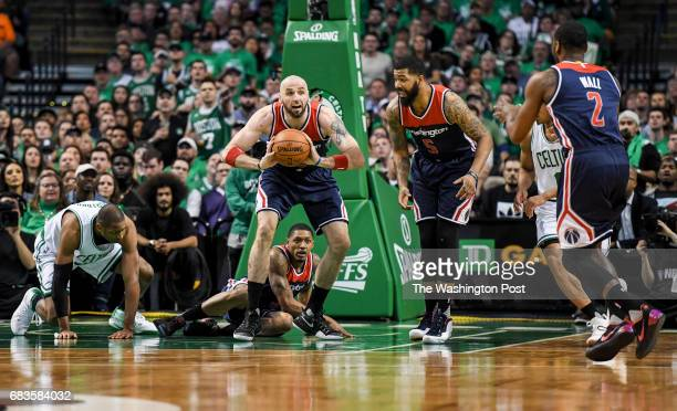 Washington Wizards center Marcin Gortat passes the ball to John Wall after grabbing the loos ball under the Boston Celtics basket during game seven...