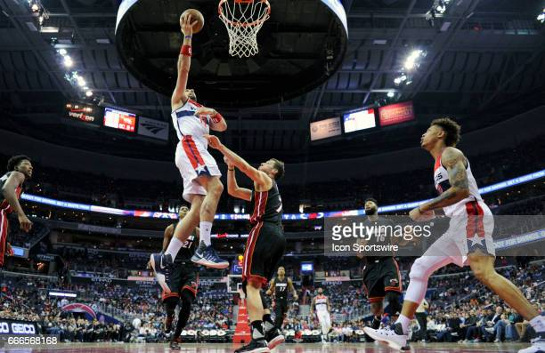 Washington Wizards center Marcin Gortat scores in the first half against Miami Heat guard Goran Dragic on April 8 at the Verizon Center in Washington...