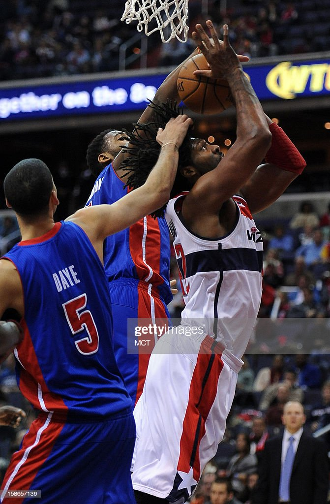 Washington Wizards center Nene (42) gets fouled by Detroit Pistons power forward Austin Daye (5), as he battles to get a shot off against Pistons center Andre Drummond (1), back, in the fourth quarter at the Verizon Center in Washington, D.C., Saturday, December 22, 2012. The Pistons defeated the Wizards, 96-87.