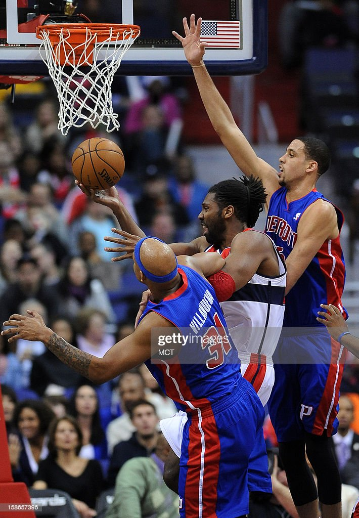 Washington Wizards center Nene (42) gets fouled by Detroit Pistons power forward Charlie Villanueva (31), as he goes to the hoop against Pistons power forward Austin Daye (5), in the first half at the Verizon Center in Washington, D.C., Saturday, December 22, 2012. The Pistons defeated the Wizards, 96-87.