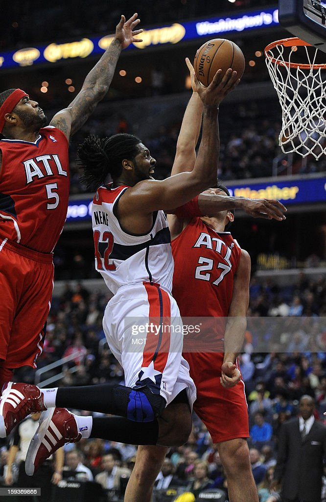 Washington Wizards center Nene (42) goes to the hoop against Atlanta Hawks small forward Josh Smith (5) and Hawks center Zaza Pachulia (27) in the third quarter at the Verizon Center in Washington, D.C., Saturday, January 12, 2013. The Wizards defeated the Hawks, 93-83.