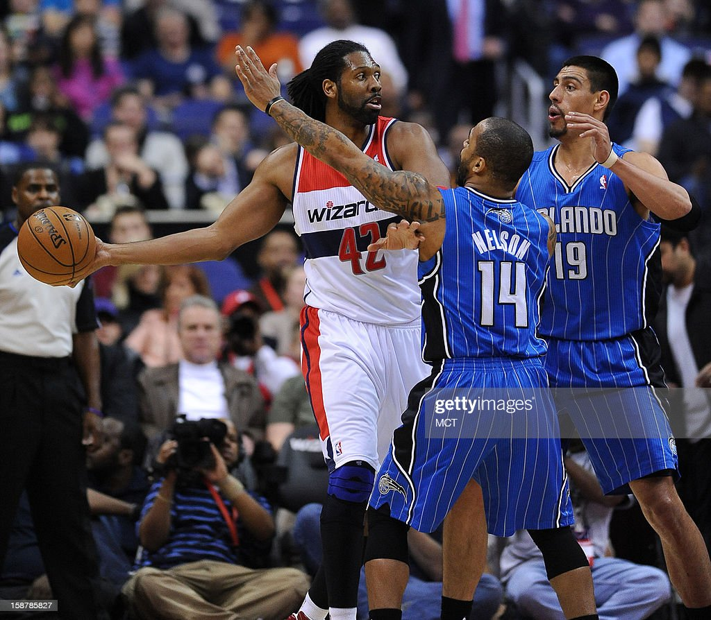 Washington Wizards center Nene (42) looks to make a pass against Orlando Magic power forward Gustavo Ayon (19) and Magic point guard Jameer Nelson (14) in the first quarter at the Verizon Center in Washington, D.C., Friday, December 28, 2012.