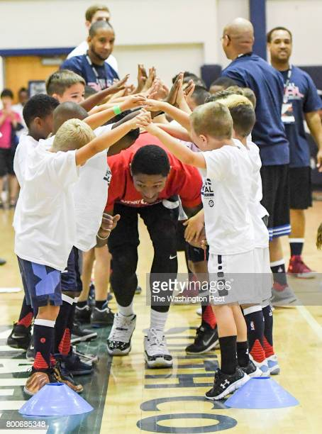 Washington Wizards guard Bradley Beal runs through a tunnel of campers as he is introduced during his basketball ProCamp in Lorton VA