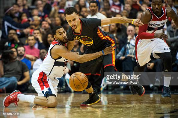 Washington Wizards guard Garrett Temple tries to get the steal from Golden State Warriors guard Stephen Curry in the first half at the Verizon Center...