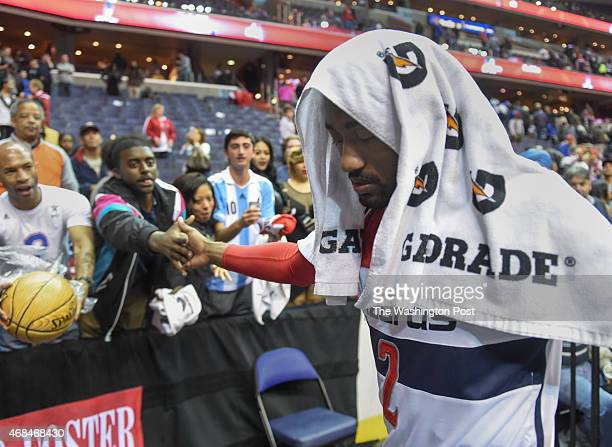 Washington Wizards guard John Wall is greeted by fans as he leaves the floor after their 10693 win over the Philadelphia 76ers on April 1 2015 in...