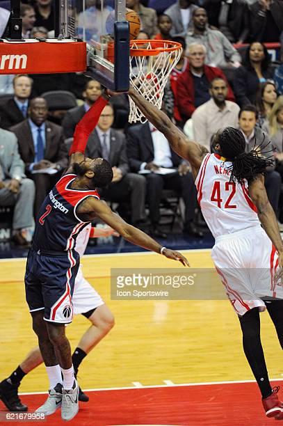 Washington Wizards guard John Wall scores against Houston Rockets center Nene Hilario on November 7 at the Verizon Center in Washington DC where the...