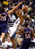 Washington Wizards guard Juan Dixon puts up a tough shot over the New Jersey Nets' Ryan Anderson during opening night action at the Verizon Center in...