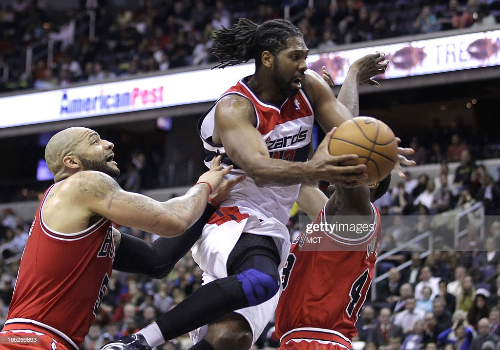 Washington Wizards' Nene, center, drives against the Chicago Bulls' Carlos Boozer, left, and Nazr Mohammed (48) in the second half at the Verizon Center in Washington, D.C., Tuesday, April 2, 2013. The Wizards won, 90-86.