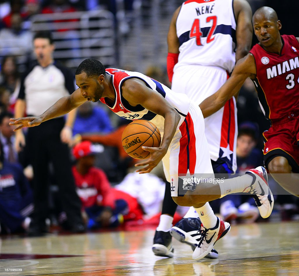 Washington Wizards point guard A.J. Price (12) falls to the floor after tripping over Miami Heat shooting guard Ray Allen (34), right, in the second quarter at the Verizon Center in Washington, D.C., Tuesday, December 4, 2012.