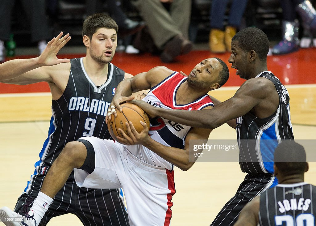 Washington Wizards point guard A.J. Price (12) is fouled by Orlando Magic power forward Andrew Nicholson (44) and center Nikola Vucevic (9) during the second half of their game played at the Verizon Center in Washington, D.C., Monday, January 14, 2013. Washington defeated Orlando 120-91.