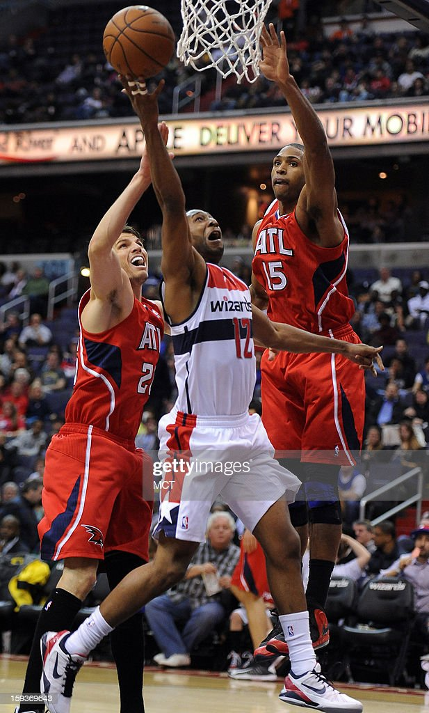 Washington Wizards point guard A.J. Price (12) puts up a shot against Atlanta Hawks shooting guard Kyle Korver (26), left, and Hawks center Al Horford (15) in the third quarter at the Verizon Center in Washington, D.C., Saturday, January 12, 2013. The Wizards defeated the Hawks, 93-83.