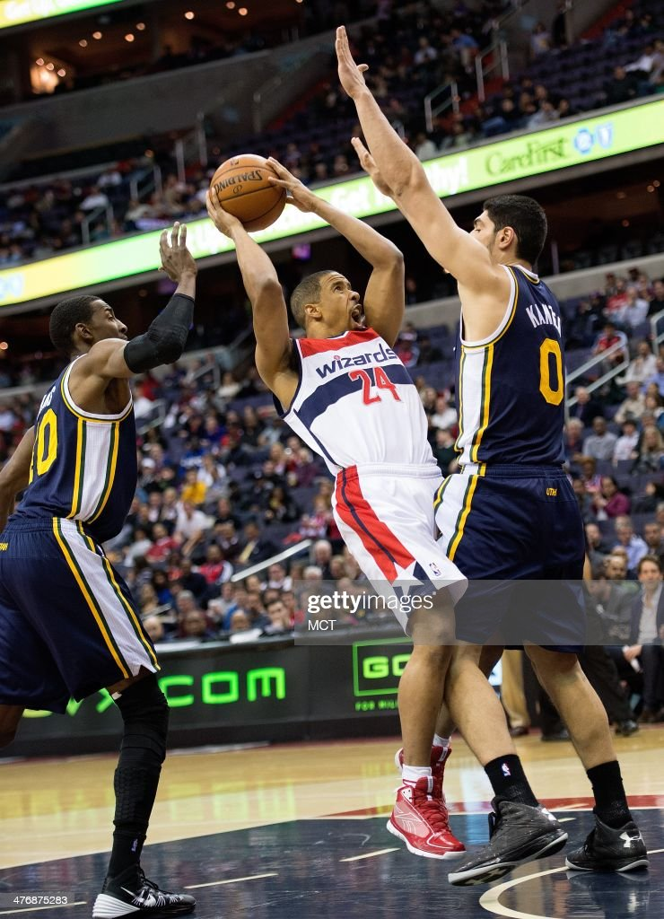 Washington Wizards point guard Andre Miller (24) tries to get a shot off between Utah Jazz point guard Alec Burks (10), left and center Enes Kanter (0) during the first half of their game played at the Verizon Center in Washington, Wednesday, Mar. 5, 2014.