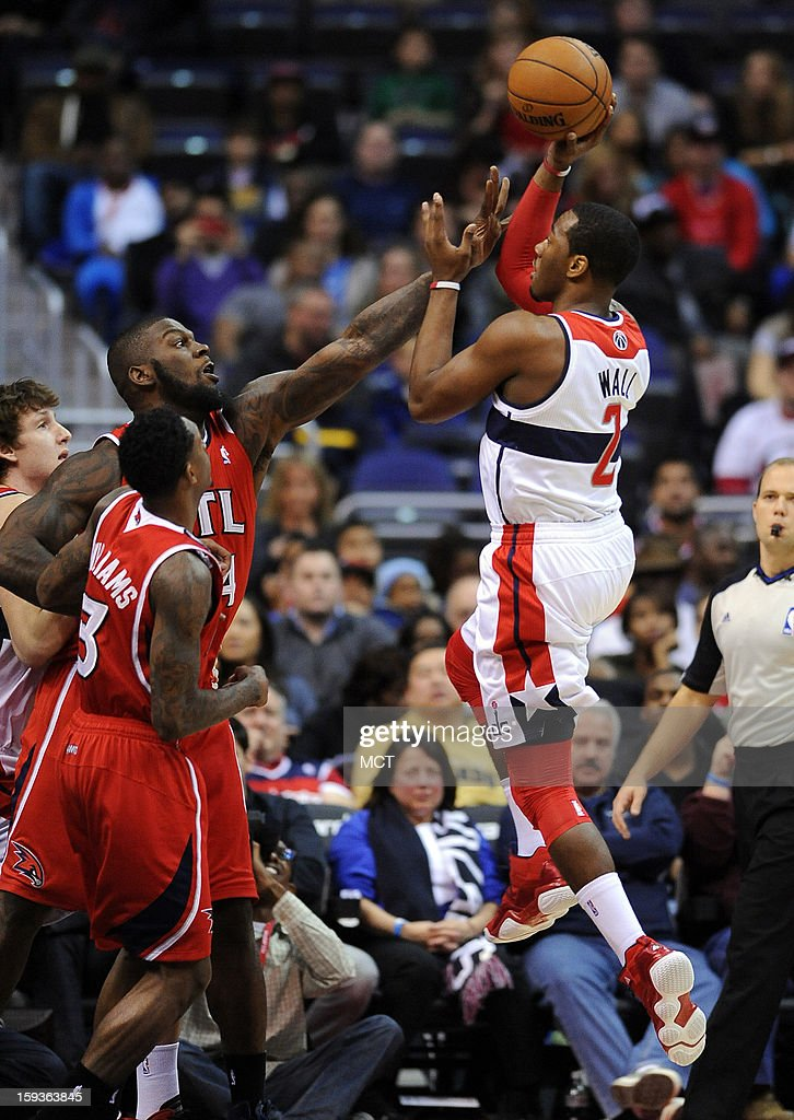 Washington Wizards point guard John Wall draws a foul on Atlanta Hawks power forward Ivan Johnson on a shot attempt in the first quarter at the...