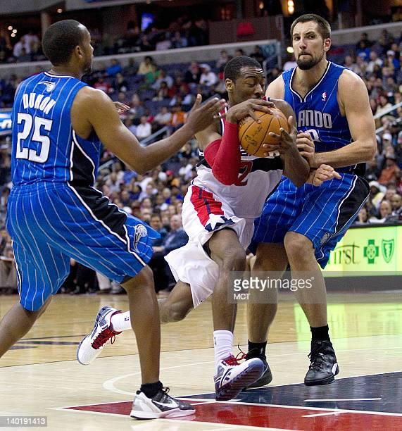 Washington Wizards point guard John Wall drives to the basket between Orlando Magic point guard Chris Duhon and power forward Ryan Anderson during...