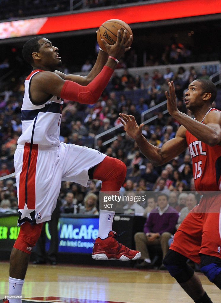 Washington Wizards point guard John Wall (2), left, lays up a score against Atlanta Hawks center Al Horford (15) in the fourth quarter at the Verizon Center in Washington, D.C., Saturday, January 12, 2013. The Wizards defeated the Hawks, 93-83.