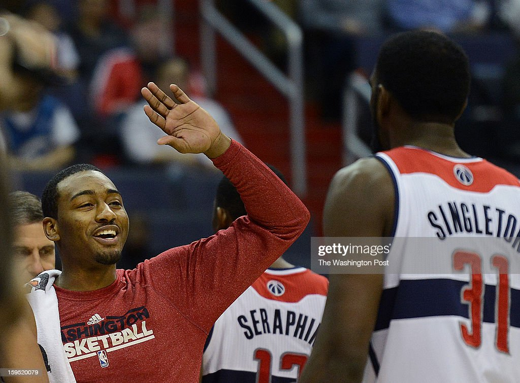 Washington Wizards point guard John Wall (2), left, offers up high fives to his teammates as they come off the court for a timeout during the game at the Verizon Center on Monday, January 14, 2013. The Washington Wizards defeated the Orlando Magic 120-91 for their third straight win.