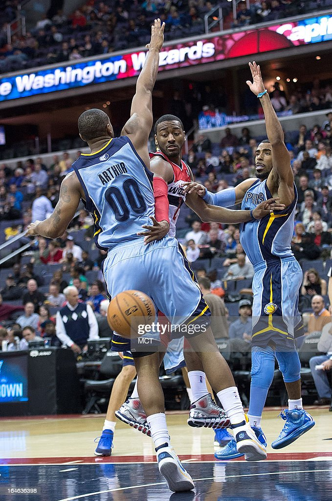 Washington Wizards point guard John Wall (2) passes the ball around the back of Memphis Grizzlies power forward Darrell Arthur (00) and in front of point guard Mike Conley (11) during the second half of their game played at the Verizon Center in Washington, D.C., Monday, March 25, 2013. Washington defeated Memphis 107-94.