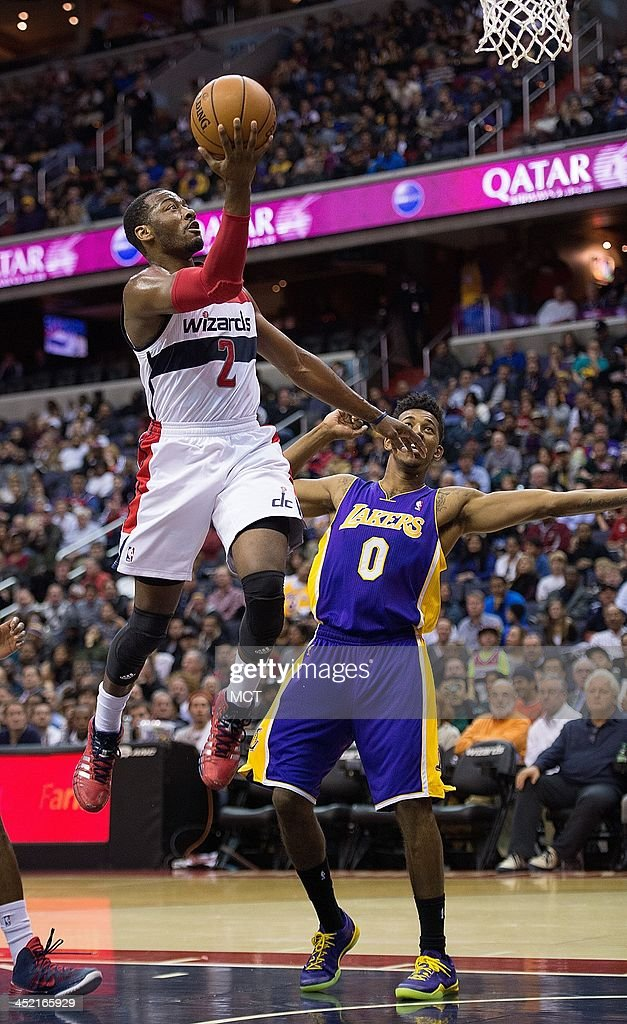 Washington Wizards point guard John Wall (2) scores after getting past Los Angeles Lakers small forward Nick Young (0) during the second half of their game played at the Verizon Center in Washington, Tuesday, November 26, 2013. Washington defeated Los Angeles 116-111.