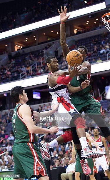 Washington Wizards point guard John Wall scores against Milwaukee Bucks center Larry Sanders as Bucks small forward Ersan Ilyasova trails on the play...