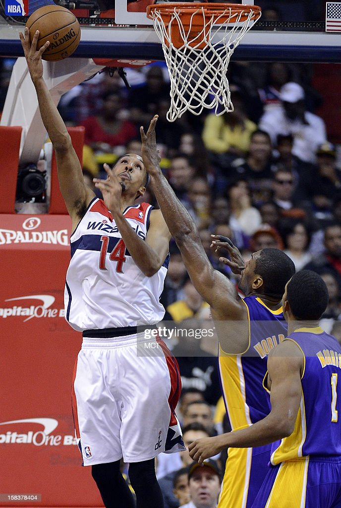 Washington Wizards point guard Shaun Livingston (14) puts up a shot against Los Angeles Lakers small forward Metta World Peace (15) and Lakers point guard Darius Morris (1) during the first half at the Verizon Center in Washington, D.C., Friday, December 14, 2012.