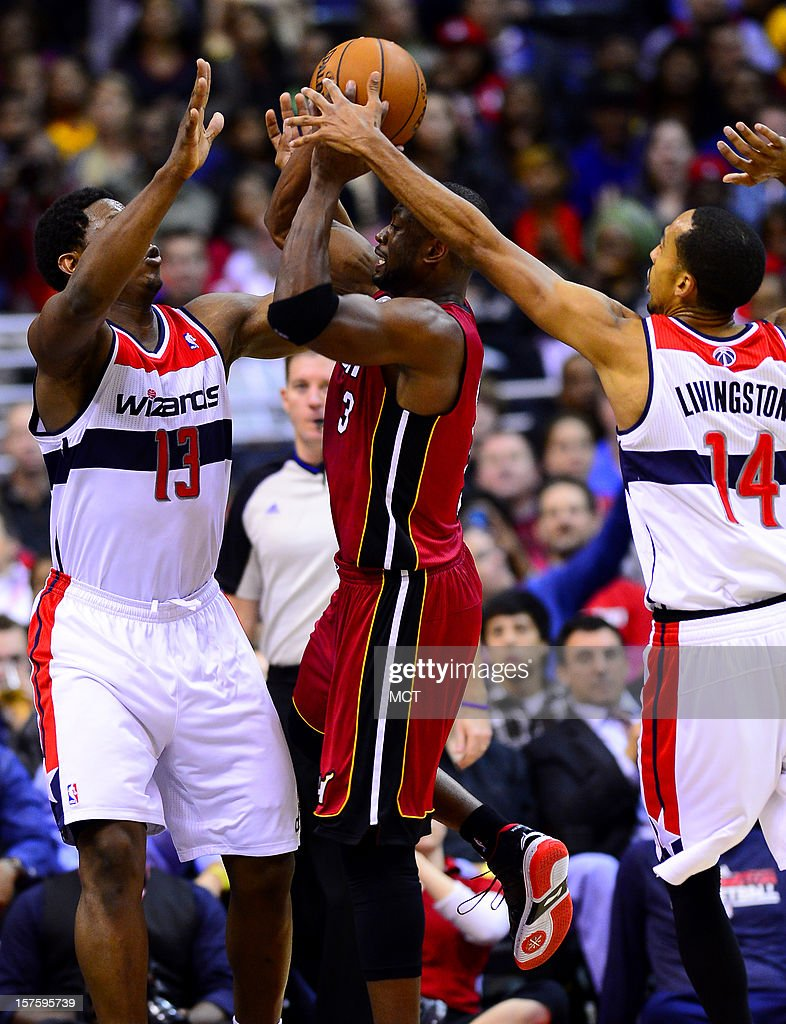Washington Wizards power forward Kevin Seraphin (13) and Wizards point guard Shaun Livingston (14) defend Miami Heat shooting guard Dwyane Wade (3) in the fourth quarter at the Verizon Center in Washington, D.C., Tuesday, December 4, 2012. The Wizards defeated the Miami, 105-101.
