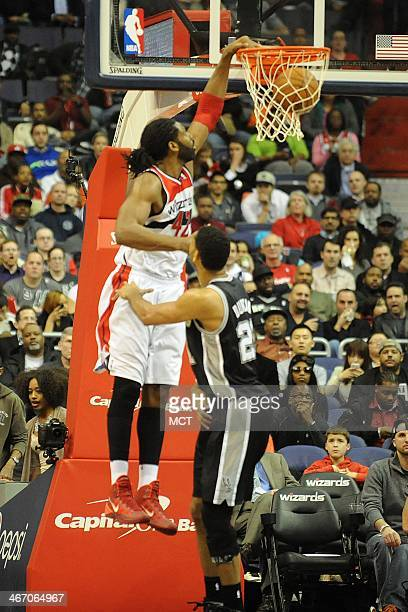 Washington Wizards power forward Nene Hilario scores a basket over San Antonio Spurs power forward Tim Duncan during the second half at the Verizon...