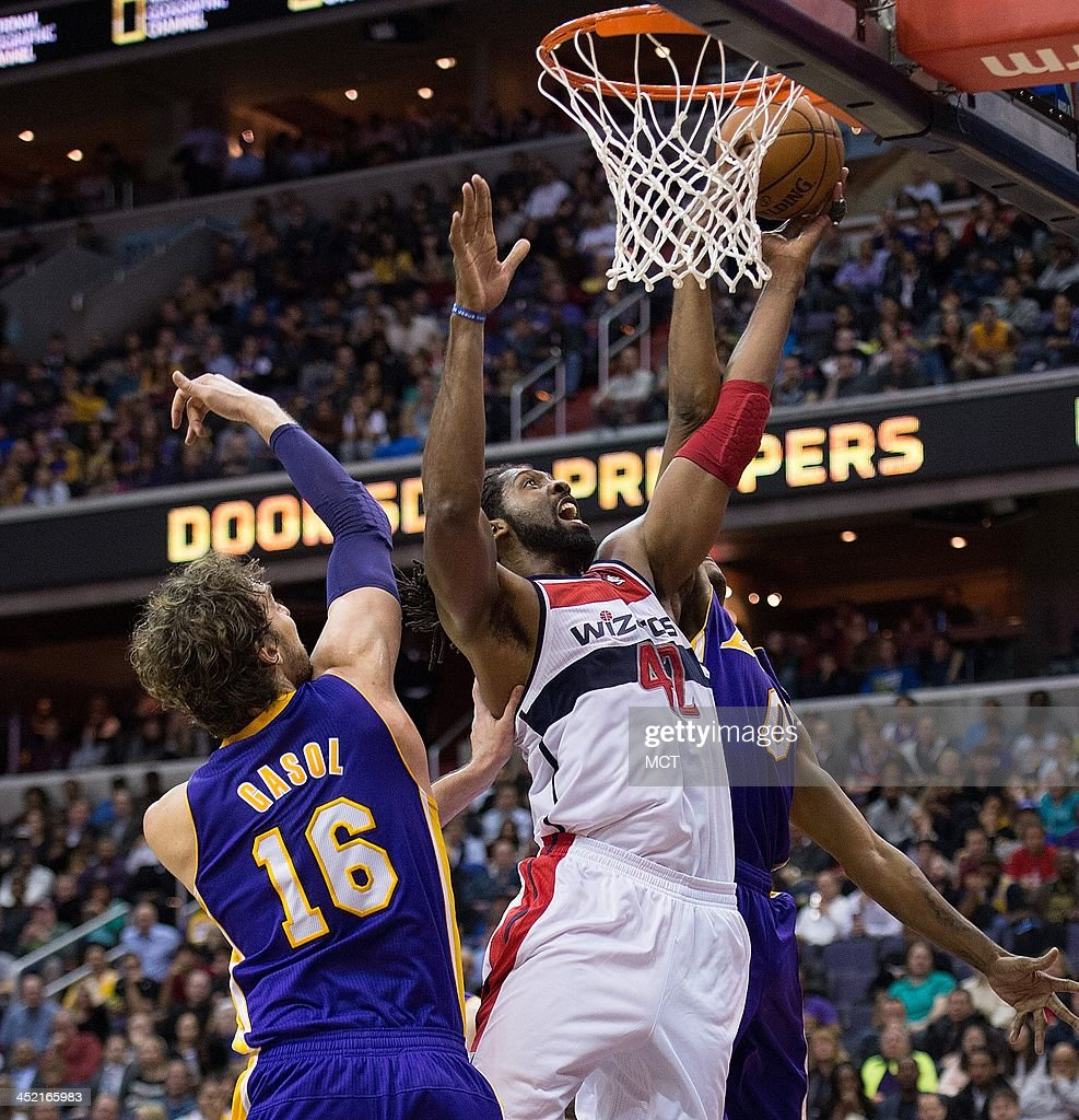 Washington Wizards power forward Nene Hilario (42) scores over Los Angeles Lakers center Pau Gasol (16), left, and small forward Nick Young (0) during the second half of their game played at the Verizon Center in Washington, Tuesday, November 26, 2013. Washington defeated Los Angeles 116-111.